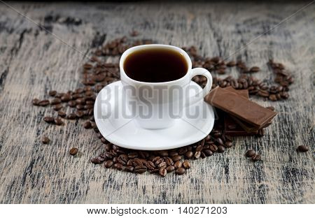 Aromatic invigorating cup of black coffee powder, chocolate and coffee beans scattered on the table