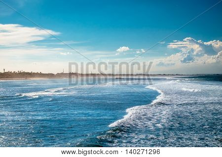 Beautiful side view of flat blue ocean waves with white foam going to the shore at sunny summer day in Bali, Indonesia