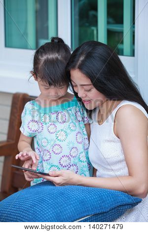 Mother And Daughter Using Digital Tablet. Family Spending Time Together At Home.