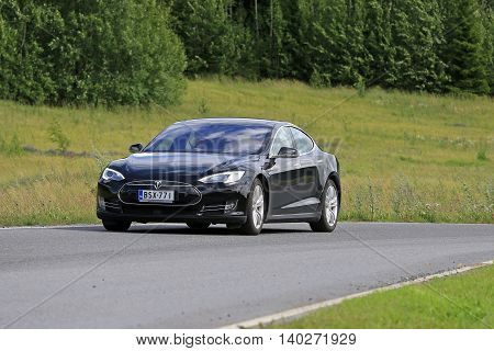PAIMIO, FINLAND - JULY 17, 2016: Black Tesla Model S electric vehicle moves on rural road through green Finnish nature at summer.