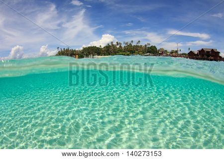 Tropical Island and sandy ocean floor. Over under half and half split photo