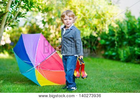 Little cute toddler boy with colorful umbrella and boots in a park