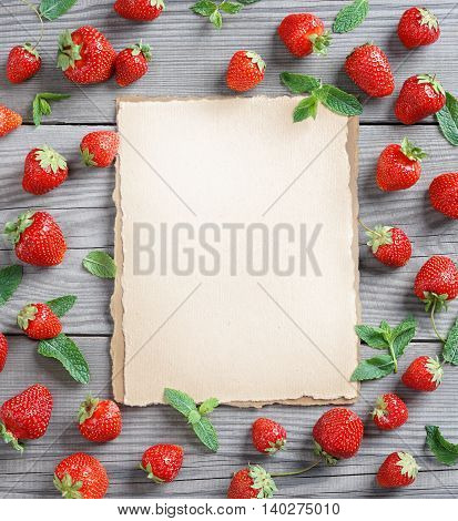 Healthy Berries background. Old paper with fresh strawberry and mint leaf on wooden table. Copy space top view high resolution product.