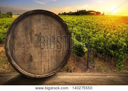 Red wine with barrel on vineyard in green Tuscany, Italy.