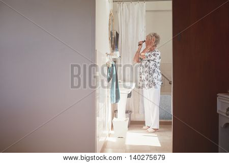 Elderly Woman Getting Ready In Bathroom