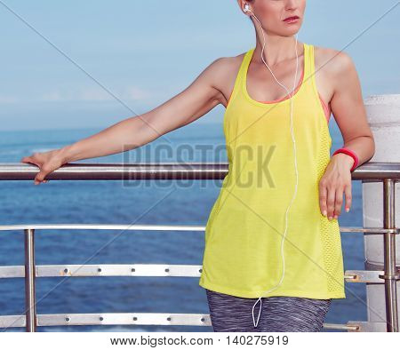 Woman In Fitness Outfit Looking Aside And Listening To Music