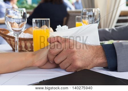 Hands of man and woman of romantic couple over a restaurant table