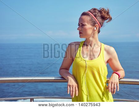 Fitness Woman Looking Into Distance And Listening To Music