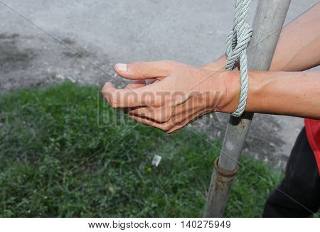 Hand tied up with rope, male with post steel