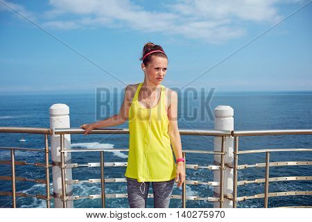 Young Fitness Woman Looking Aside And Standing At Embankment
