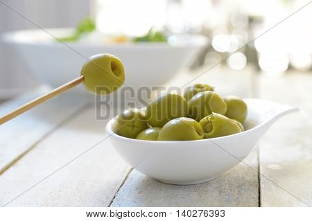 Typical Spanish tapas. Some stuffed olives served on a plate on a white wooden table. Empty copy space for Editor's text.