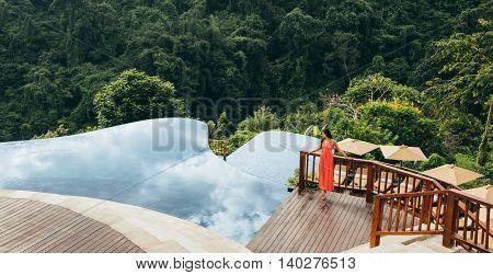 Woman Near Infinity Swimming Pool In Nature