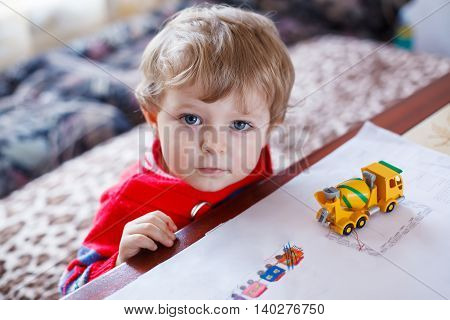 Little toddler boy with blue eyes playing with toy, inddor