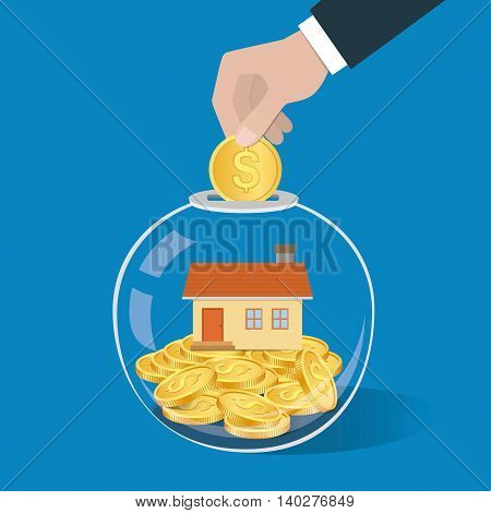 Money Saving Concept. Hand Putting A Coin Into Glass Bottle. Saving To Buy A House Or Home.