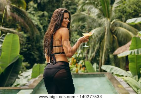 Smiling Young Female With Cocktail At Poolside