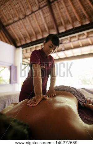 Shot of female massage therapist massaging man at day spa. Man getting back massage at spa resort.