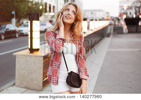 Beautiful young blonde woman flirt with boyfriend by a phone on the street city.