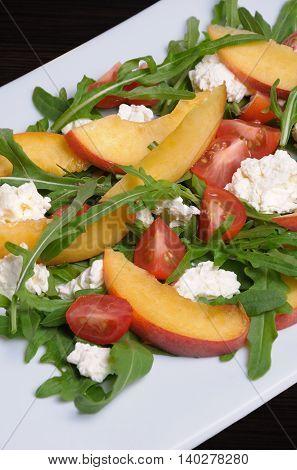Salad with slices of peach cherry tomatoes arugula feta