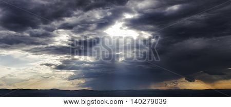 Rays of light shining through clouds over landscape