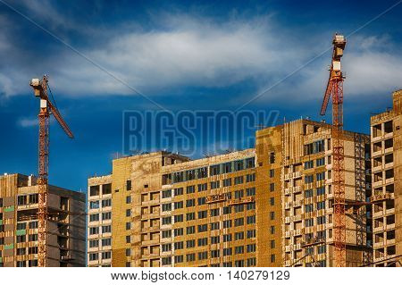 Crane and building construction on the background of expressive blue sky