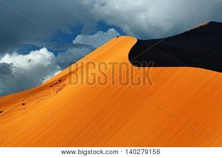 Beautiful landscape with big red dune 40 against dramatic sky at sunrise Sossusvlei Namib Naukluft National Park Namibia