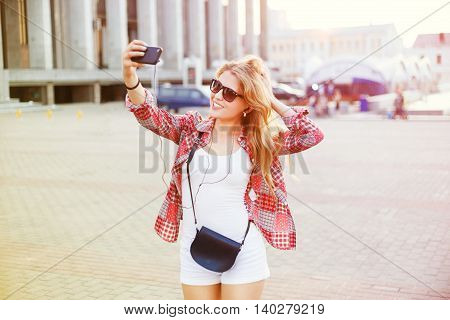 Young beautiful blonde woman photographed themselves on phone