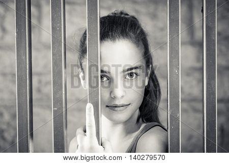 Black And White Portrait Of A Teenage Girl Behind Metal Bars