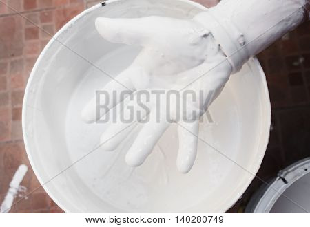 Painter mixing white, hand with colors mix, painted home in the work