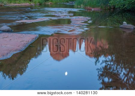 moonrise over cathedral rock reflected in oak creek sedona arizona