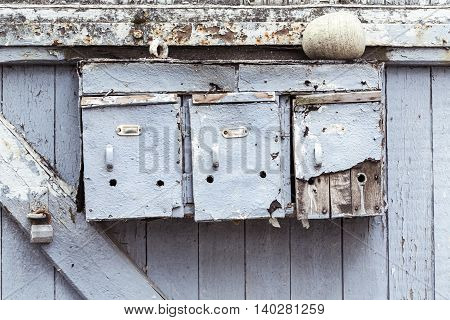 Three Very Old And Grungy Mailboxes At A Gate