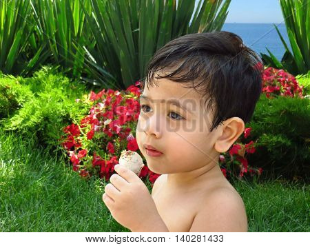 Boy eats ice-cream in a hot summer day in a garden with a view on a sea