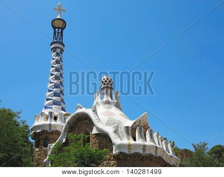 Barcelona Spain 05 july 2016: The entrance of Park Guell with the famous mosaics of Antonio Gaudi over blue sky background.