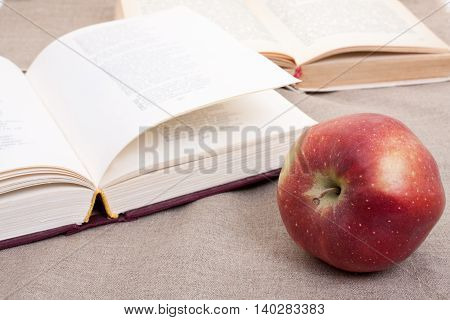 Composition With Red Apple And Opened Books On The Table, On The Decorative Linen Cloth.
