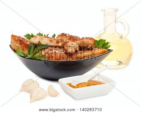Fried Chicken Pieces Coated With Breadcrumbs With With Parsley On A Black Plate, Garlic, A Bottle Of