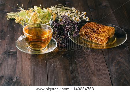 Liquid Honey With Honeycomb And Tea Cup Inside Bunch Of Dry Herbs Over White Wooden Surface