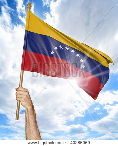 Person's hand holding the Venezuelan national flag and waving it in the sky, 3D rendering