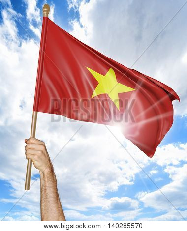 Person's hand holding the Vietnamese national flag and waving it in the sky, 3D rendering