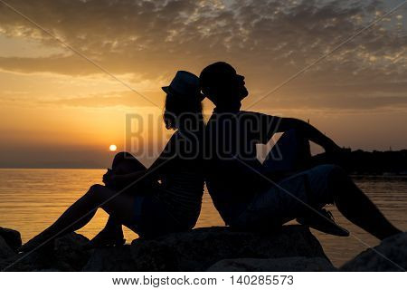 Couple in love sitting on the rocks near the sea on their summer vacation enjoying a beautiful sunset