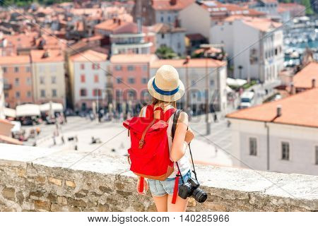 Young female traveler with hat, red backpack and photo camera enjoying the view on Piran old town. Back view with copy space. Traveling in Slovenia
