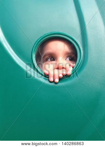 authentic image of toddler girl looking through a hole at a playground