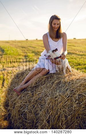 young girl in a white dress is sitting with a Jack Russell Terrier dog on the haystack during a summer sunset