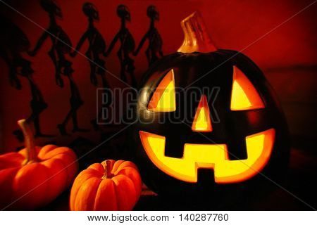 Halloween decorations - jack o lantern with small pumpkins and skeleton background