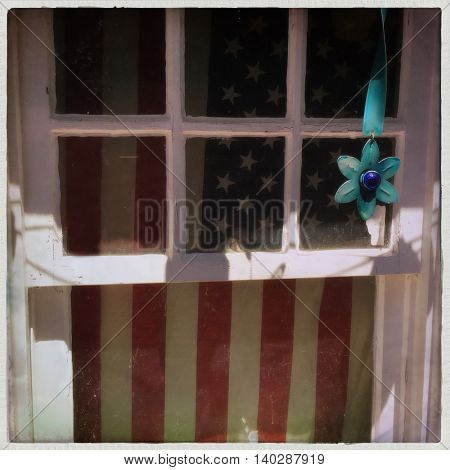 American flag hanging from an old window 4th of July- Memoial Day - Veterans Day - vintage instagram filtered effect