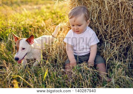 gay boy kid blonde in white tank top sitting on a field of hay next to the stack with the dog during sunset