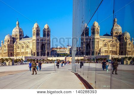 MARSEILLE, FRANCE - MAY 22, 2015:  Sunny spring morning in Marseille. Cathedral of Saint Mary Major is reflected in the mirrored wall of a building