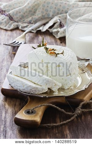 Traditional homemade cottage cheese in a plate on the old wooden background. Helpful dairy products. Selective focus