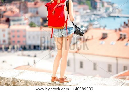 Young female traveler with red backpack and photo camera staying in front of Piran old town. Traveling in Slovenia