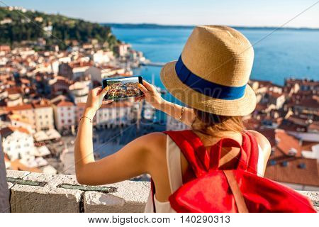 Young female traveler with red backpack and photo camera enjoying the view on Piran old town. Traveling in Slovenia