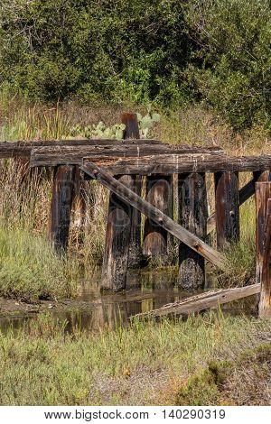 Old destroyed abundant wooden bridge and creek