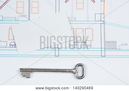 Architectural project, blueprints, silver key with house figure and blank business card on wooden background. Real Estate Concept. Top view
